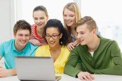 Estudantes de sorriso que olham o portátil na escola Fotos de Stock