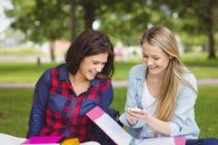 Estudantes de sorriso que usam o smartphone imagens de stock