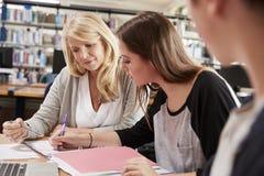 Estudantes de Working With College do professor fêmea na biblioteca fotos de stock
