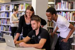 Estudantes diversos na biblioteca do terreno da faculdade imagem de stock
