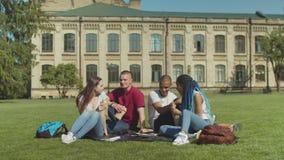 Estudantes diversos novos que comem o petisco no gramado do terreno video estoque