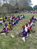 Estudantes do esporte que sentam-se na grama para a classe do esporte imagem de stock