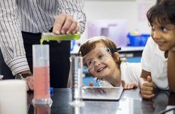 Estudantes do jardim de infância que aprendem no laboratório da experiência da ciência imagens de stock