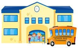 Estudantes e ônibus escolar na frente da escola Fotografia de Stock Royalty Free