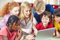 Estudantes e professor que usa o Internet imagens de stock royalty free