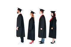 Estudantes em tampões acadêmicos e em vestidos da graduação que estão em seguido Foto de Stock