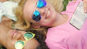 Estudantes fêmeas alegres que encontram-se na grama, em fotos de vista no telefone e no sorriso vídeos de arquivo