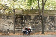 Estudantes fêmeas alegres que sentam-se no banco com professor, portátil, pa Fotos de Stock