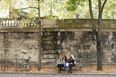 Estudantes fêmeas alegres que sentam-se no banco com professor, portátil, pa Imagens de Stock Royalty Free