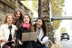 Estudantes fêmeas alegres que sentam-se no banco com professor, portátil, pa Imagem de Stock