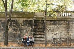 Estudantes fêmeas alegres que sentam-se no banco com professor, portátil, pa Foto de Stock Royalty Free