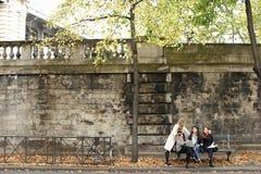 Estudantes fêmeas alegres que sentam-se no banco com professor, portátil, pa Fotos de Stock Royalty Free