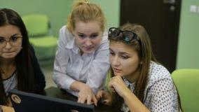 Estudantes fêmeas e masculinos novos que sentam-se na mesa, trabalhando com PC, olhando o monitor, a discussão e a preparação vídeos de arquivo