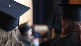 Estudantes fêmeas em tampões acadêmicos que escutam a leitura na cerimônia de graduação vídeos de arquivo