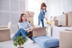 Estudantes fêmeas otimistas que desembalam e que limpam a sala do dormitório imagem de stock