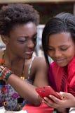 Estudantes fêmeas pretos que olham em um telefone celular Fotografia de Stock