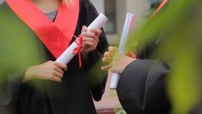 Estudantes fêmeas que guardam diplomas e que conversam no parque, ensino superior filme