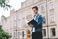 Estudantes felizes bem sucedidos que estão o terreno ou a universidade próxima fora fotografia de stock