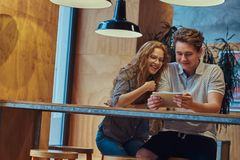 Estudantes felizes dos pares que usam uma tabuleta digital ao sentar-se em uma tabela na cantina da faculdade durante uma ruptura fotos de stock