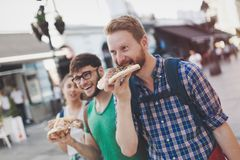 Estudantes felizes que comem a pizza na rua Fotografia de Stock
