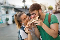 Estudantes felizes que comem a pizza na rua Foto de Stock
