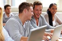 Estudantes felizes que conversam na classe Imagens de Stock