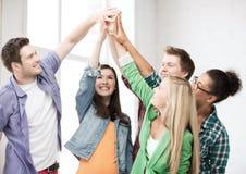 Estudantes felizes que dão a elevação cinco na escola foto de stock royalty free