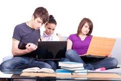 Estudantes felizes que olham o portátil fotografia de stock