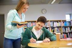 Estudantes felizes que preparam-se aos exames na biblioteca Imagens de Stock
