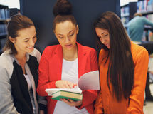 Estudantes fêmeas novos que compartilham de um livro na biblioteca Fotos de Stock