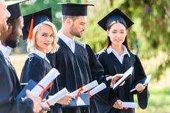 estudantes graduados bem sucedidos nos cabos e em guardar dos chapéus fotografia de stock