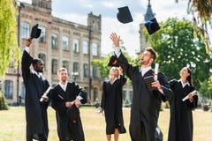 estudantes graduados felizes novos que jogam acima tampões da graduação foto de stock royalty free