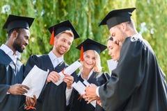 estudantes graduados novos felizes nos cabos imagens de stock