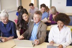 Estudantes maduros na classe da educação para adultos com professor fotos de stock royalty free