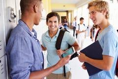 Estudantes masculinos da High School pelos cacifos que olham o telefone celular fotografia de stock royalty free