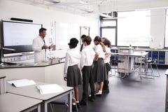 Estudantes masculinos de Teaching High School do tutor da High School que vestem uniformes na classe da ciência foto de stock royalty free