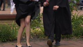 Estudantes masculinos e fêmeas felizes que dançam e que têm o divertimento após a cerimônia de graduação vídeos de arquivo