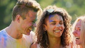 Estudantes masculinos e fêmeas felizes que gracejam, rindo e tendo o divertimento no festival da cor filme