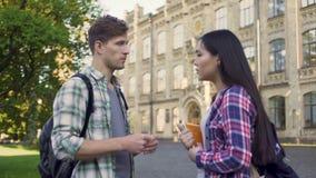 Estudantes multirraciais que discutem o teste perto do terreno, do homem e da fala fêmea video estoque
