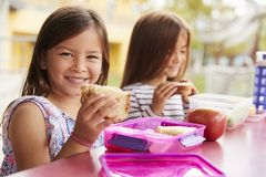 Estudantes novas que guardam sanduíches na tabela do almoço escolar imagem de stock