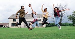 Estudantes novos bem sucedidos no terreno que olham a câmera e o sorriso e em cinco altos ao saltar no ar livre fotografia de stock