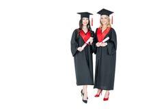 Estudantes novos bonitos nos tampões acadêmicos que guardam diplomas e que sorriem na câmera Imagens de Stock