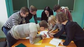 Estudantes novos com uma escrita e a discussão do professor de algo na sala de aula filme