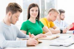 Estudantes novos e espertos que aprendem em uma sala de aula Foto de Stock
