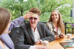Estudantes novos engraçados que têm o divertimento, colando papéis nas testas em um fundo do café Conceito do jogo do nome Fotografia de Stock