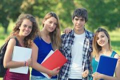 Estudantes novos felizes do retrato no parque Fotografia de Stock