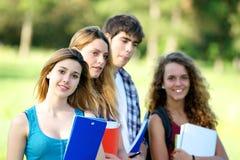 Estudantes novos felizes do retrato no parque imagens de stock royalty free