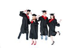 Estudantes novos felizes nos tampões da graduação com salto dos diplomas isolados Fotografia de Stock Royalty Free
