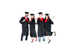 Estudantes novos felizes nos tampões da graduação com salto dos diplomas isolados Imagem de Stock Royalty Free