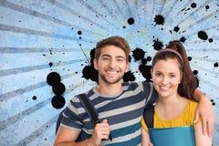Estudantes novos felizes que estão contra o fundo chapinhado azul Fotografia de Stock Royalty Free